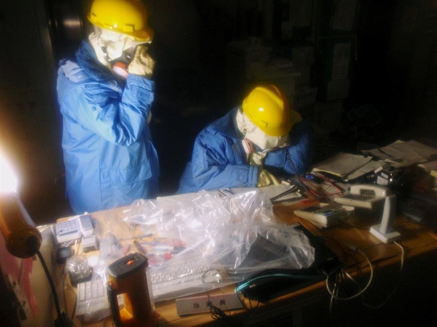 Arbeiter im AKW Fukushima betrachten einen Schaltplan